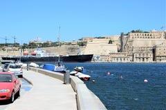 Senglea, Malta, em julho de 2015 Ideia das fortificações da capital da ilha no outro lado e no navio de carga de passagem fotos de stock