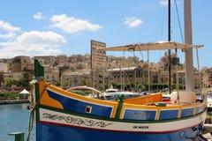 Senglea Malta, Juli 2016 Berömd maltesisk fiskebåt på bakgrunden av den gamla staden fotografering för bildbyråer