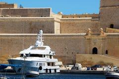Senglea Malta, Juli 2016 Stärkte väggar med ingångsportar och en stor yacht på pir royaltyfria bilder