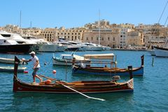 Senglea, Malta, July 2016. Man on a boat in which tourists are rolled. to the harbor of the city. royalty free stock photos