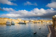 Senglea, Malta - Panoramic vew of yachts and sailing boats mooring at Senglea marina in Grand Canal of Malta. On a bright sunny summer day woth blue sky and Royalty Free Stock Photo