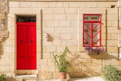 Senglea, Malta - Traditional red door and window of an old maltese house at Senglea. On a sunny summer day Royalty Free Stock Photography