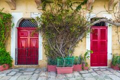 Senglea, Malta - Traditional red doors and houses on the streets of Senglea. With leaves Stock Images