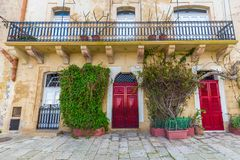 Senglea, Malta - Traditional red doors and houses on the streets of Senglea. With plants and leaves Stock Photography