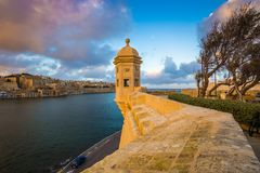 Senglea, Malta - Watch tower of Fort Saint Michael, Gardjola Gardens with the city of Valletta. And beautiful sky and clouds at sunset Stock Photos