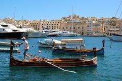 Senglea, Malte, juillet 2016 Homme sur un bateau en lequel des touristes sont roulés au port de la ville photos libres de droits