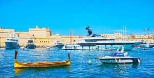 Small luzzu boats and posh yachts in Vittoriosa marina, Senglea, Malta. Senglea seaside promenade is the nice place to overlook Vittoriosa port with a view on royalty free stock photography