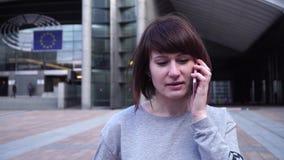 A senhora é de passeio e de fala no telefone perto do Parlamento Europeu em Bruxelas bélgica video estoque