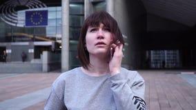 A senhora é de passeio e de fala no telefone perto do Parlamento Europeu em Bruxelas bélgica Movimento lento filme
