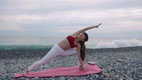 A senhora é treinando ele corpo por asanas da ioga na costa de mar em Pebble Beach no dia filme