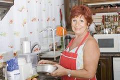 Senhora 65 anos de funcionamento velho na cozinha imagens de stock royalty free