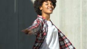 Senhora afro-americana encaracolado-de cabelo nova que sorri e que dança na rua, vida feliz filme