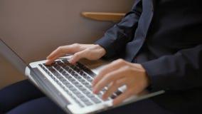 A senhora agradável do negócio está sentando-se pela janela no trem e no texto de datilografia no portátil video estoque