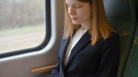 A senhora agradável nova do negócio está datilografando o texto em um portátil ao ir pelo trem vídeos de arquivo