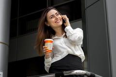 Senhora alegre do escritório que mantém um café disponivel e que fala no telefone imagens de stock royalty free