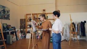 A senhora alegre está pintando a imagem junto com seu artista profissional de professor fêmea que usa pinturas da escova e de óle video estoque