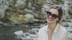 A senhora alegre olha na câmera e nos sorrisos docemente, menina com os óculos de sol na camisa leve branca do às bolinhas, jovem video estoque