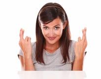 Senhora alegre que cruza seus dedos ao sorrir imagem de stock