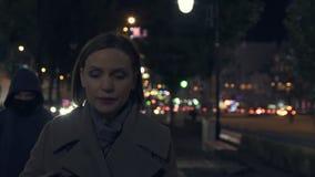 A senhora amedrontada é seguida seja ladrão na capa na rua escura da cidade, crime urbano filme