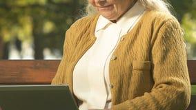 Senhora aposentada de sorriso que datilografa lentamente o portátil, descanso exterior, Internet da consultação filme
