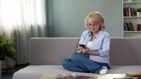 Senhora aposentada nos vidros que sentam-se no sofá, vídeo de observação do smartphone em linha fotografia de stock