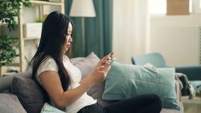 A senhora asiática atrativa está usando o smartphone para fazer o pagamento em linha com o cartão de banco que senta-se no sofá e filme
