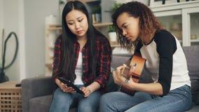 A senhora asiática está usando o portátil para ensinar seu amigo afro-americano jogar a guitarra que aprende em casa junto As men video estoque