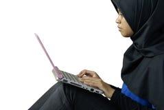 Senhora asiática muçulmana séria que usa o portátil foto de stock