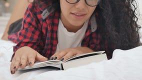 A senhora atrativa lê o livro na cama filme