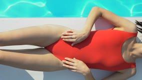 Senhora atrativa magro no roupa de banho vermelho que encontra-se perto da associação e que toma sol, proteção solar video estoque