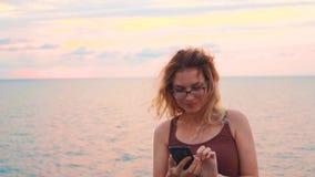 A senhora atrativa nova bonito no t-shirt marrom faz a foto de sua cara na frente do mar frio e o por do sol cor-de-rosa, menina  video estoque
