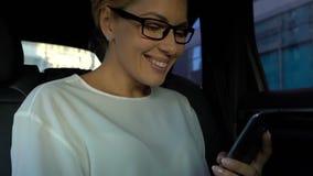 Senhora bem sucedida que lê a mensagem das bom-notícias no telefone celular durante a movimentação do carro, alegria filme