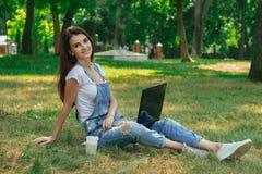 Senhora bonita alegre que senta-se na grama no parque com um portátil fotos de stock