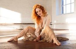 Senhora bonita com cabelo vermelho ondulado longo na pose assentada Fotografia de Stock