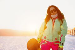 Senhora bonita com o snowboard contra a inclinação do esqui do por do sol Foto de Stock Royalty Free