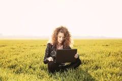 Senhora bonita com seu portátil na grama Fotos de Stock