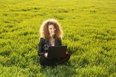 Senhora bonita com seu portátil na grama Fotografia de Stock