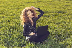 Senhora bonita com seu portátil na grama Fotografia de Stock Royalty Free