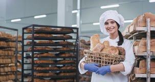 Senhora bonita de sorriso com uma cesta grande do pão cozido fresco na frente da câmera em uma fábrica da padaria ela que olha bo filme