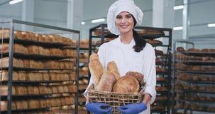 Senhora bonita de sorriso da fábrica do alimento grande na seção de cozimento ela que guarda um pão cozido fresco e que olha em l vídeos de arquivo