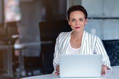 Senhora bonita do negócio com o laptop no escritório fotografia de stock