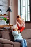 Senhora bonita do novo-adulto que põe levemente a mão sobre o ombro da mãe imagem de stock