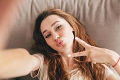 A senhora bonita emocional surpreendente faz o selfie fazer o gesto da paz foto de stock royalty free