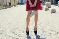 Senhora bonita encantador no vestido vermelho, com o saco nas mãos, em h preto fotografia de stock royalty free
