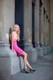 A senhora bonita inclina-se contra colunas em um vestido Foto de Stock