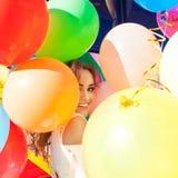 Senhora bonita no equipamento retro que guarda um grupo dos balões no th Imagem de Stock Royalty Free