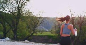 A senhora bonita no meio da montanha bebe alguma água sedento, a seguir continua seu exercício através da montanha video estoque