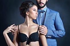 Senhora bonita no sutiã com o indivíduo considerável no terno Foto de Stock Royalty Free