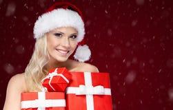 A senhora bonita no tampão do Natal guarda um grupo de presentes Imagens de Stock