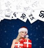 A senhora bonita no tampão do Natal guarda um grupo de presentes para amigos Imagem de Stock